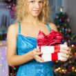 Girl in a blue dress with a gift on Christmas tree background — Stock Photo #41427383