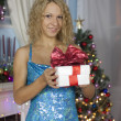 Girl in a blue dress with a gift on Christmas tree background — Stock Photo #42730501