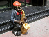 Play an instrument of character sculpture in front of a restaura — Stock Photo