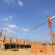 Tower crane and unfinished building under the blue sky — Stock Photo