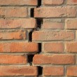 Crack of red brick wall - Stok fotoğraf