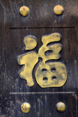 Golden chinese characters in brown gate — Stockfoto