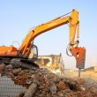 Excavator in the construction debris clean up site - Stock Photo