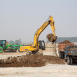 Stock Photo: Excavator and transporter