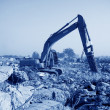 Excavator in construction debris cleup site — Stock Photo #35519859