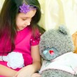 Girl looking at teddy bear — Stock Photo