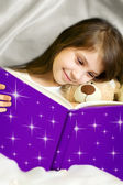 Little girl reading book with her toy bear — Stockfoto