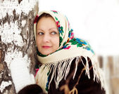 Woman in a painted shawl at a birch in winter — Stok fotoğraf