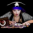 Girl pirate looking at jewelry — Stock Photo #23449678