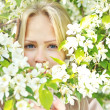 Closeup beautiful  woman face among blossom  tree branches — Stock Photo