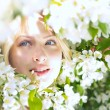 Closeup beautiful woman among blossom apple tree — Stock Photo