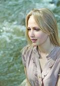 Beautiful blonde woman looking at river — Stock Photo