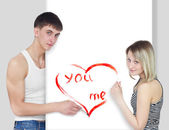 Young couple draws red heart on white — Stock Photo