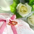 Wedding gold rings on a pillow with bouquet — Stock Photo