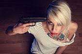 Suicidal young woman with tears and gun pointed at head — Stock Photo