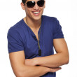 Happy handsome young man wearing dark sunglasses — Stock Photo