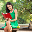 Beautiful young woman with toothy smile reading book in the park — Stock Photo