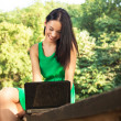 Attractive young woman with toothy smile using laptop outdoors. — Стоковое фото