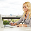 Stock Photo: Business womwith toothy smile using laptop outdoors