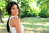 Portrait of beautiful happy young black haired woman in a park — ストック写真