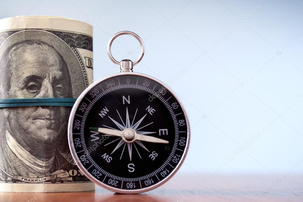 American dollars and compass on a blue gradient background — Stock Photo #18305191