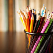 Wire desk tidy full of coloured pencils — Stock Photo