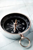 Handheld compass on a map — Stock Photo