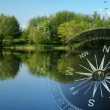 Постер, плакат: Magnetic compass over a tranquil lake