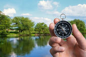 Man navigating the countryside with a compass — Stock Photo