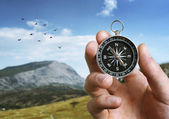 Man holding a compass over a landscape view — Stock Photo