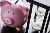 Piggy bank with an hour glass — Stock Photo