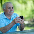 Senior man reading a text message on his phone — Stock Photo