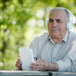 Elderly man listening to music on a tablet — Stock Photo #47358841