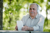 Elderly man listening to music on a tablet — Stock Photo