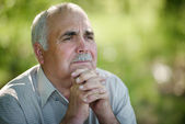 Elderly man sitting thinking — Stock Photo
