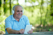 Senior man searching for a tune on his MP3 player — Stock Photo