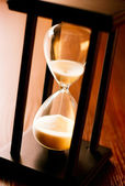 Wooden hourglass with running sand — Stock Photo