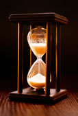 Illuminated hourglass in a wooden frame — Stock Photo