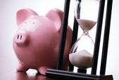Pink piggy bank with a vintage hourglass behind — Stock Photo