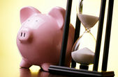 Pink piggy bank with a vintage hourglass behind — Stockfoto
