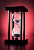 Egg timer or hourglass on a red background — Stock Photo