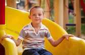 Attractive little boy on a slide in a playground — Stock Photo