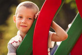 Cute little boy in a colorful kids playground — Stock Photo