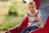 Small boy playing on a slide in a kids playground — Stock Photo