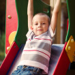 Cute little boy about to take a ride on a slide — Stock Photo #51796835