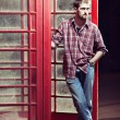 Young man standing at telephone box — Stock Photo