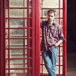 Young man standing at telephone box — Stock Photo #13370631
