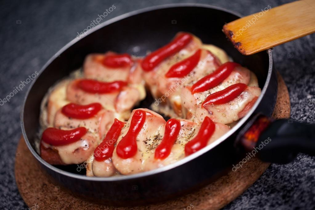 Hot sausages with cheese and ketchup in pan — Stock Photo #13371263