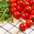 Tomatoes and rucola on towel — Stock Photo #14165024
