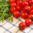 Tomatoes and rucola on towel — Stock Photo